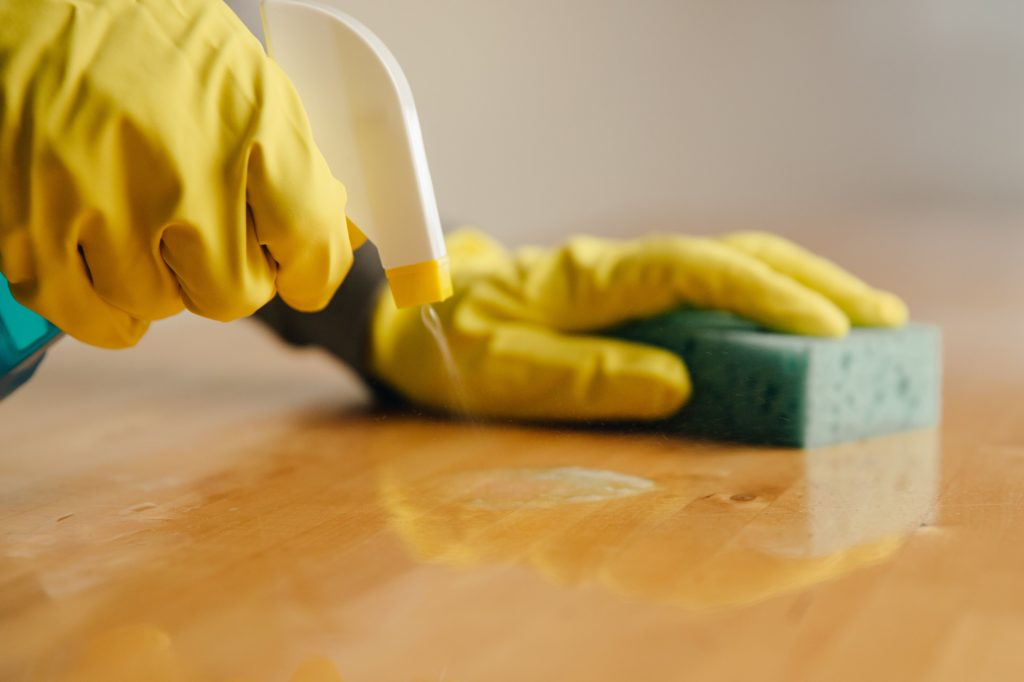 Cleaner being sprayed onto a wood surface by gloved hands holding a sponge.
